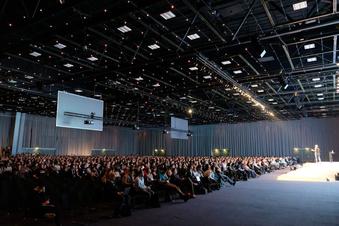 a large conference room full of people that mostly look like white male, with a speaker on a large stage illuminated in white